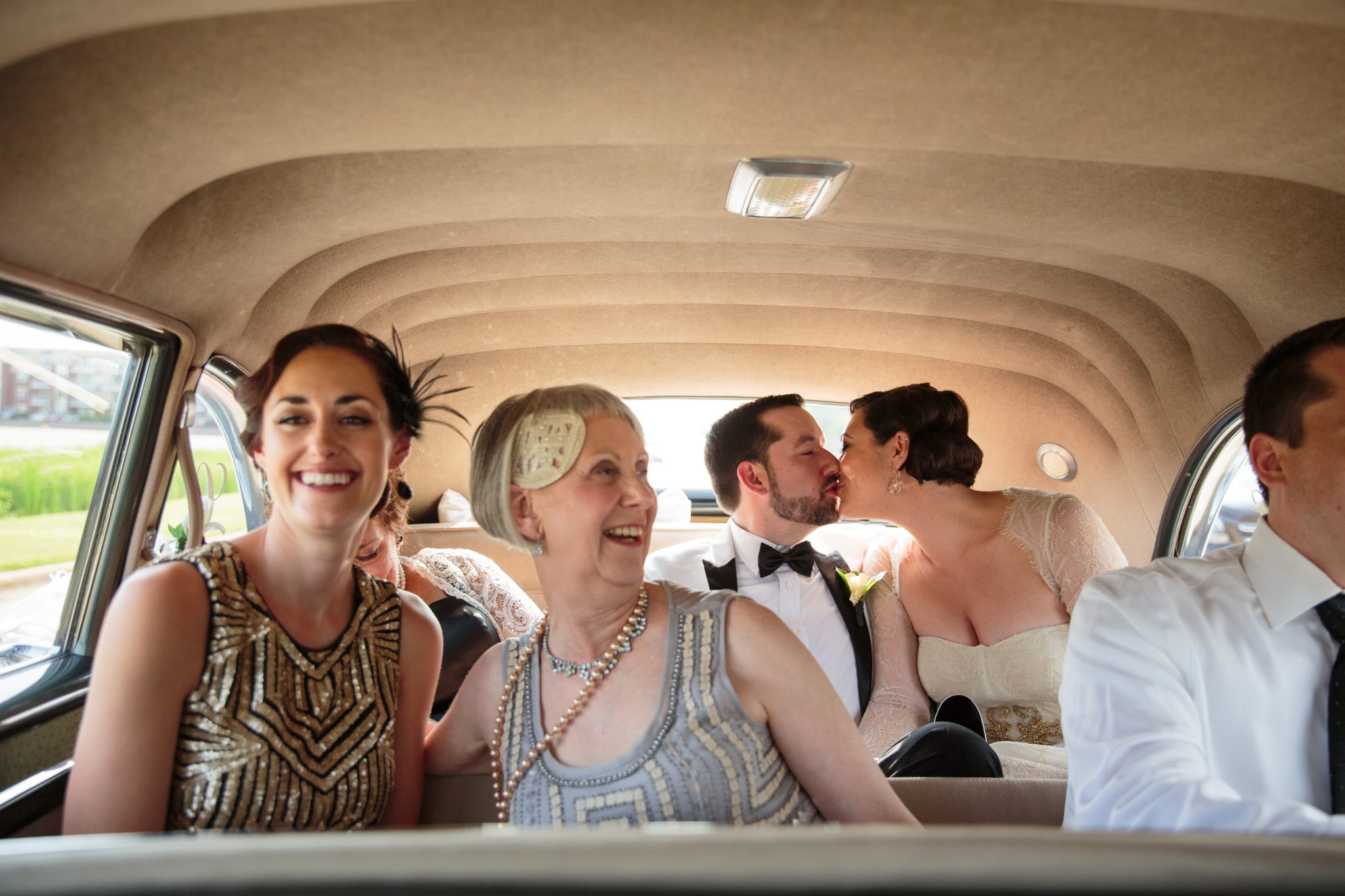 A newlywed couple kisses in the back seat of a vintage limousine