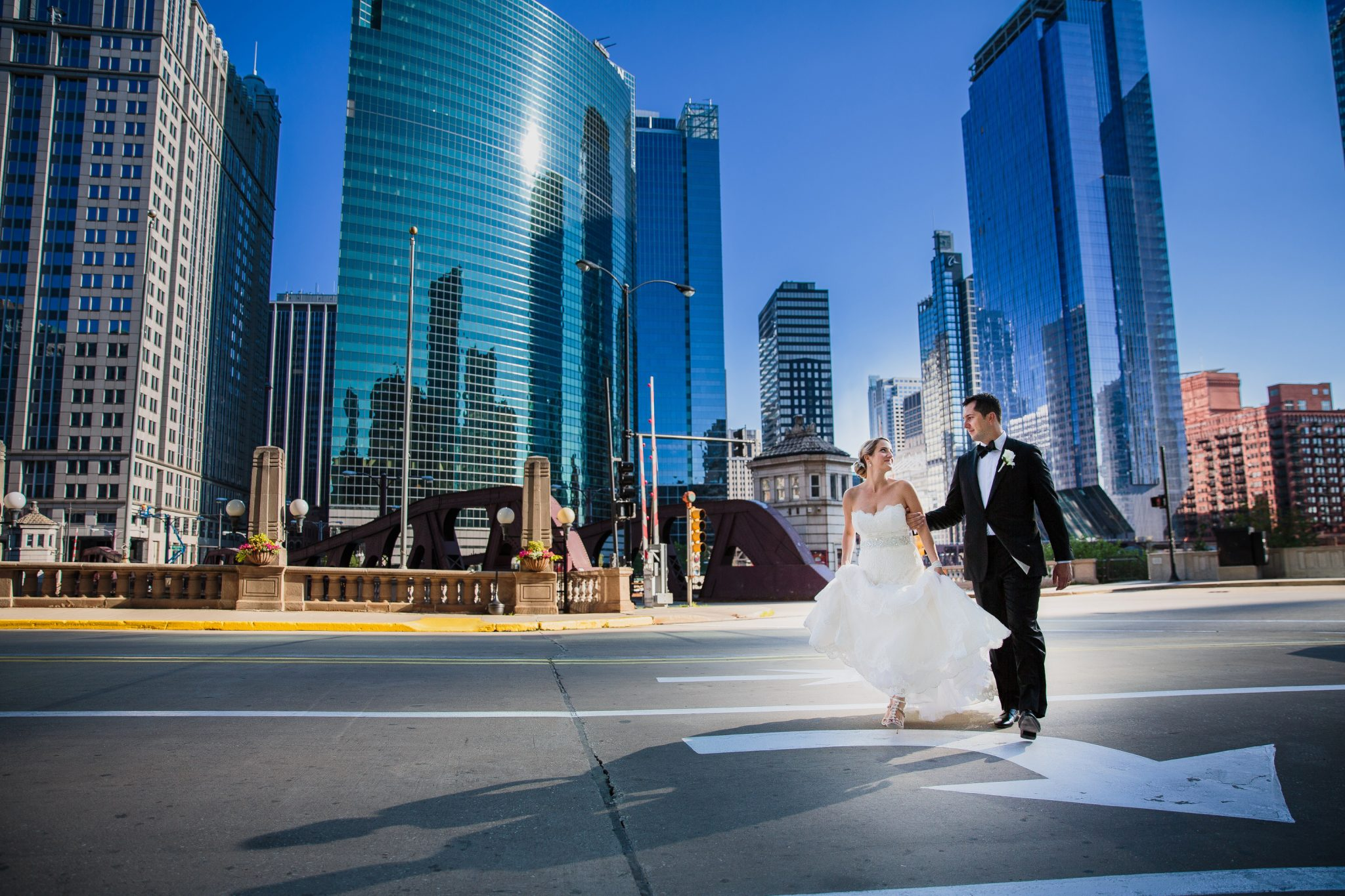 A Chicago bride and groom walk the city streets hand in hand.